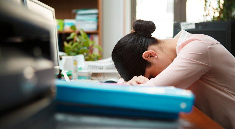 Die Nebentätigkeit der Mitarbeiterin fordert ihren Tribut- Kollegin schlafend am Arbeitspaltz